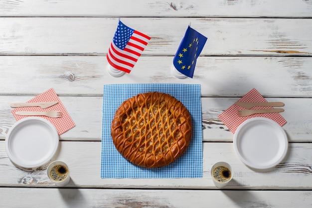 Drapeaux à côté de la tarte et des assiettes. drapeaux de table américains et européens. l'hospitalité unit les gens. faites une pause dans la politique.