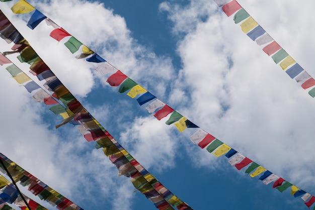 Drapeaux du népal sur ciel bleu clair avec des cumulus pour l'attraction de voyage de tourisme