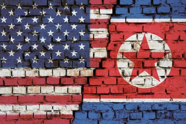Drapeaux des états-unis et de la corée du nord sur le mur de briques avec une grande fissure au milieu