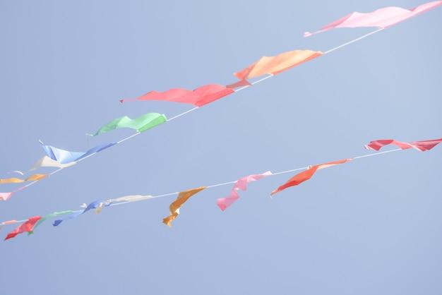 Drapeaux de fête colorés banderoles suspendus sur un ciel bleu pour la décoration de vacances