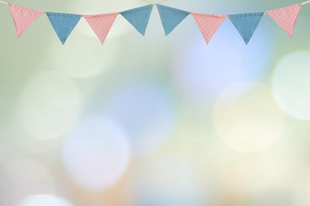 Drapeaux de fête colorés suspendus sur flou fond abstrait, fond de carte de voeux