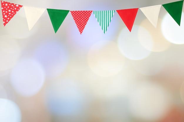 Drapeaux de fête colorés suspendus sur flou fond abstrait