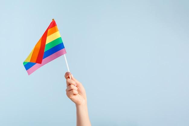 Drapeaux gays dans la main des femmes sur fond gris