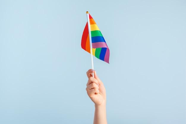 Drapeaux gays dans la main des femmes sur gris