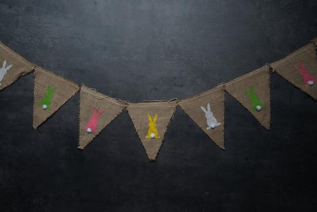 Drapeaux en lin avec des lapins de pâques sur fond de pierre sombre