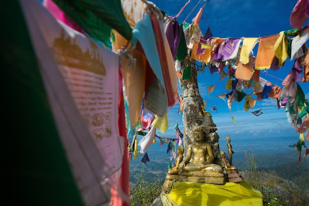 Drapeaux de mantra et statue de bouddha sur doi nork au parc national de doi luang, phayao
