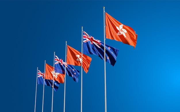 Les drapeaux de la nouvelle-zélande et de hong kong volent ensemble dans le vent contre le ciel bleu