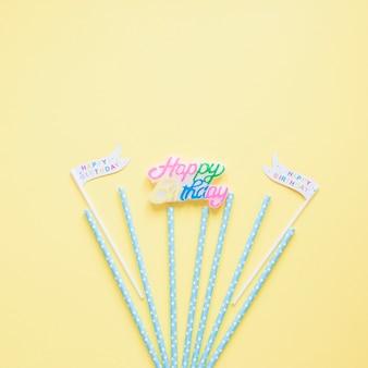 Drapeaux et pailles près d'écriture d'anniversaire