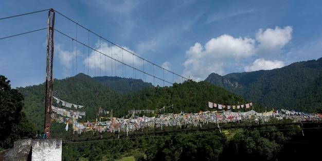 Drapeaux de prière suspendus au-dessus du pont suspendu, punakha, punakha valley, district de punakha, bhoutan