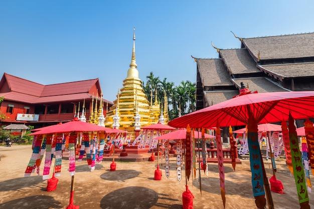 Drapeaux de prières suspendus avec un parapluie ou un drapeau traditionnel du nord accroché à une pagode dans le temple phan tao