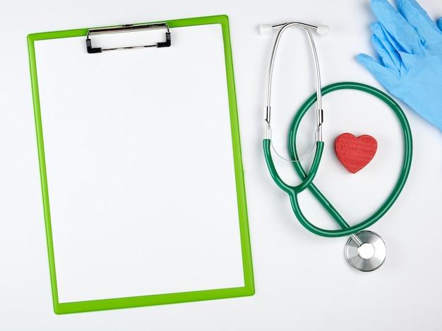 Draps blancs vides et stéthoscope médical sur blanc
