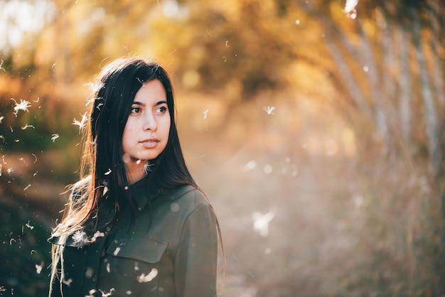Dreamy belle fille en duvet blanc sur fond de bokeh avec des feuilles jaunes au soleil doré.