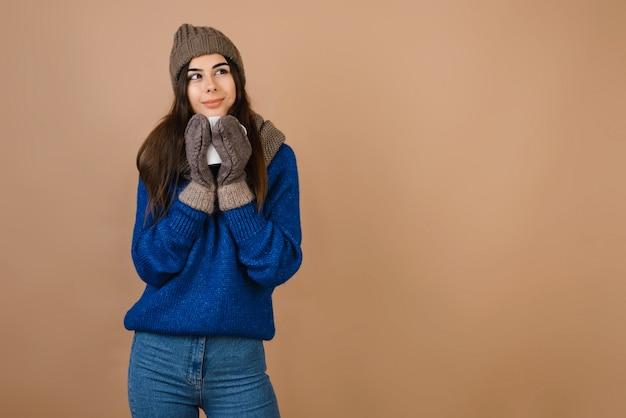 Dreamy, douce fille au chapeau et des gants tenant une tasse