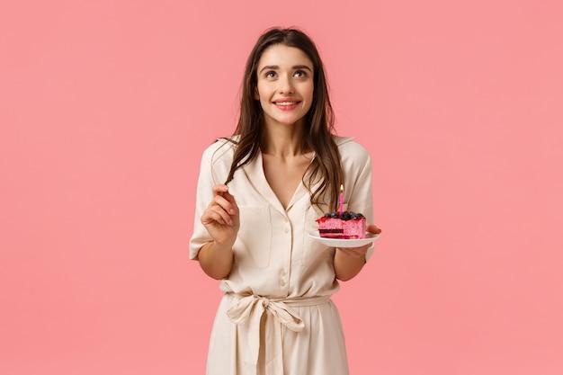 Dremy cute, female brunette female holding cuillère et assiette, rêver, sourire tout en levant