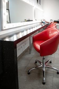Dressing lumineux avec chaises rouges. une simple pièce pour le maquillage plusieurs fauteuils confortables sont alignés.