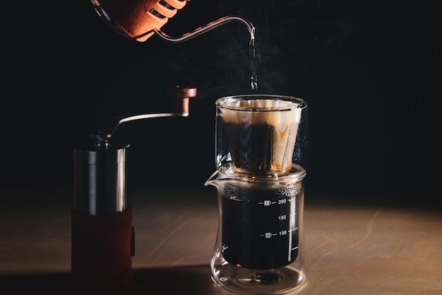 Drip brew coffee tasse à saveur de filtre à caféine. l'homme renverse de l'eau chaude prépare un café filtré