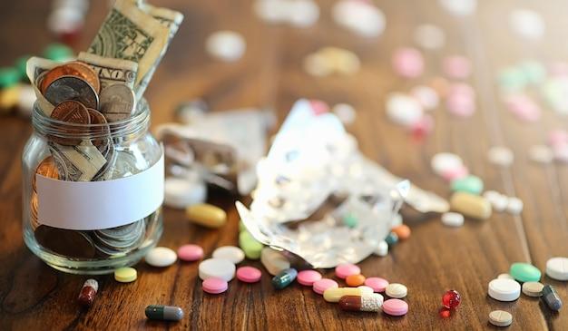 Drogues et pièces de monnaie dans un bocal en verre sur un plancher en bois. économies de poche des pièces de monnaie dans une banque pour les services médicaux. tirelire dans un bocal en verre avec des pièces de monnaie.