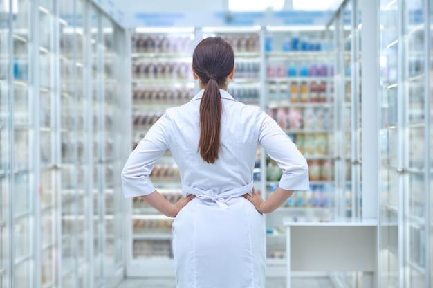 Droguiste caucasien regardant des étagères avec des compléments alimentaires