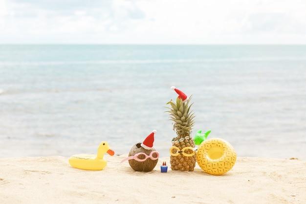 Drôle d'ananas attrayant et de noix de coco dans des lunettes de soleil élégantes sur le sable contre la mer turquoise. porter des chapeaux de noël.