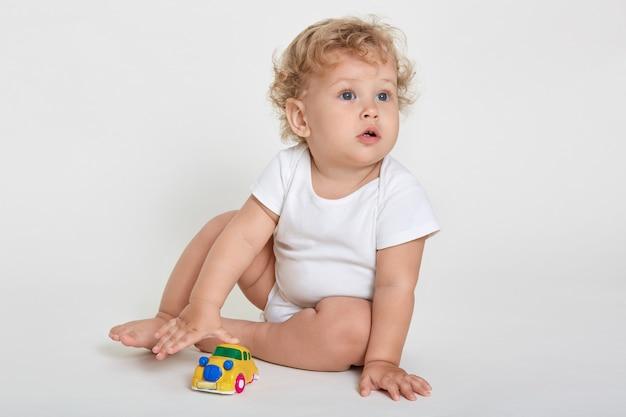 Drôle de bébé garçon jouant jouet dans la crèche ou la maternelle, bébé blond aux cheveux bouclés en costume de corps assis sur le sol pieds nus