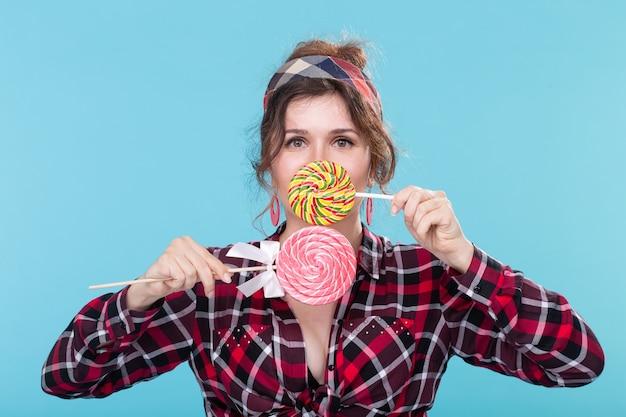 Drôle belle jeune femme aux yeux exorbités ferme sa bouche avec des sucettes colorées posant sur un mur bleu. concept d'amour et desserts riches en calories.