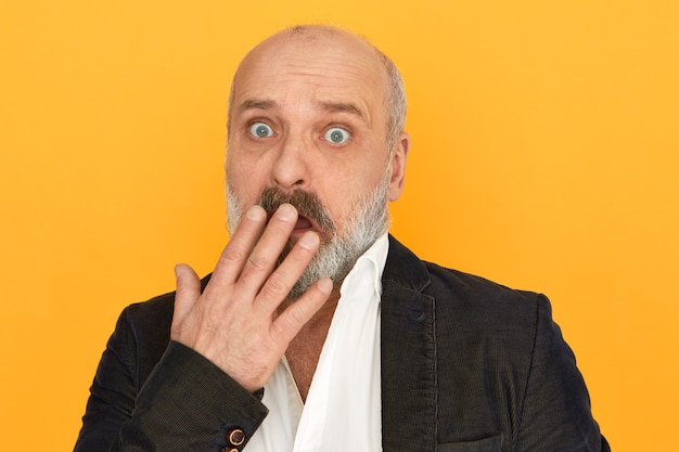 Drôle de bogue aux yeux surpris retraité masculin avec une barbe épaisse haletant couvrant la bouche avec la main, recevant de mauvaises nouvelles inattendues, ayant une expression faciale effrayée et perplexe