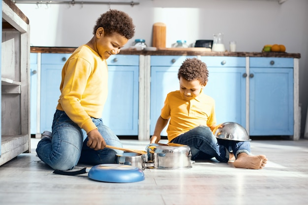 Drôle de cacophonie. de petits enfants optimistes assis sur le sol de la cuisine et jouant du tambour sur des casseroles, se faisant passer pour des musiciens professionnels