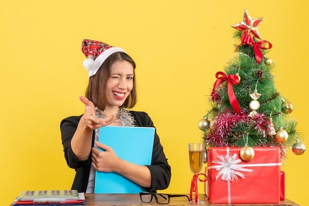 Drôle charmante dame en costume avec chapeau de père noël et décorations de nouvel an tenant un document au bureau sur jaune isolé