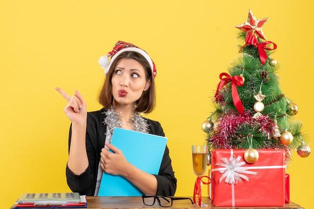 Drôle charmante dame en costume avec chapeau de père noël et décorations de nouvel an tenant un document de réflexion profondément dans le bureau sur jaune isolé