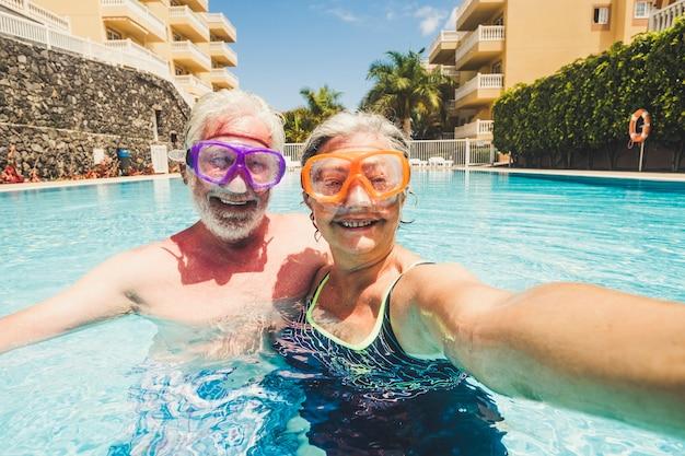 Un drôle de couple de personnes d'âge mûr prend une photo de selfie pendant qu'il s'amuse et s'amuse à la piscine de la résidence - un style de vie heureux à la retraite avec un couple âgé en activité de loisirs d'été ensemble