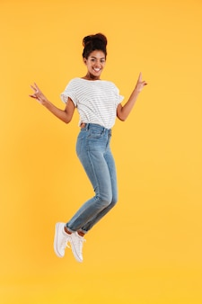 Drôle dame joyeuse africaine sautant et souriant isolé