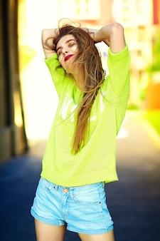 Drôle élégant sexy souriant belle jeune femme modèle en été hipster jaune vif tissu dans la rue
