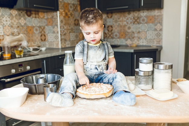 Drôle enfant assis sur la table de la cuisine dans une cuisine roustique jouant avec de la farine et dégustant un gâteau.