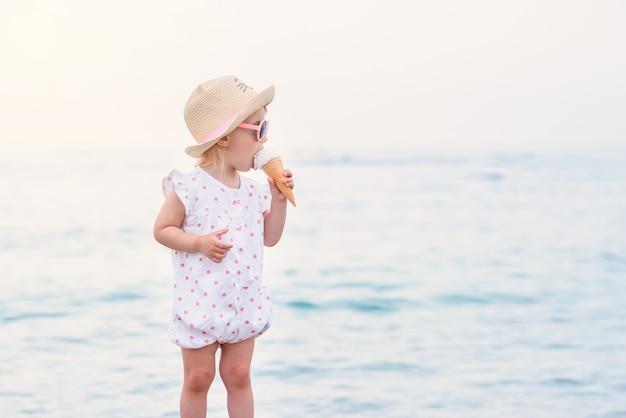 Drôle enfant en bas âge portant une salopette d'été rose, un chapeau et des lunettes de soleil roses mange de la glace blanche à la vanille pendant les vacances sur la plage de la mer.
