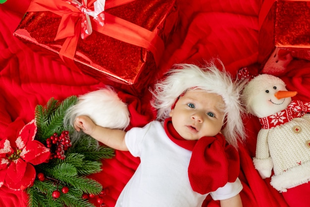 Un drôle d'enfant dans un costume de père noël se trouve sur un fond rouge parmi les cadeaux