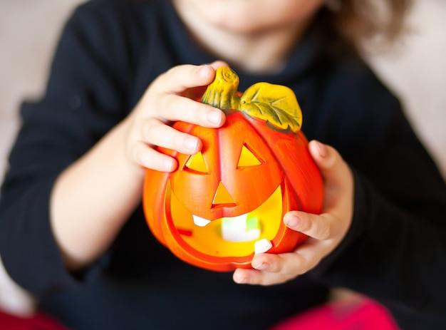 Drôle enfant fille en costume de sorcière pour halloween avec citrouille jack dans une mains