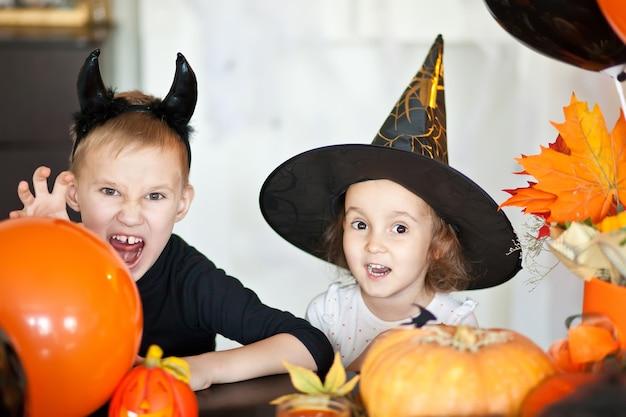 Drôle enfant fille et garçon adolescent en sorcière et costumes maléfiques pour la fête d'halloween