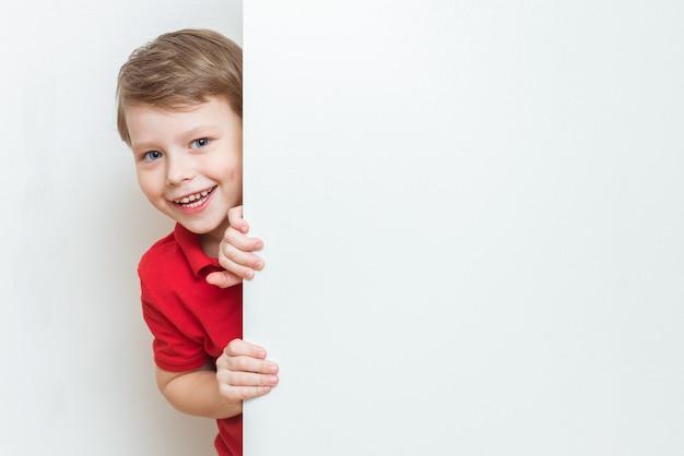 Drôle enfant garçon se cachant derrière un panneau publicitaire blanc vierge avec copie espace et furtivement