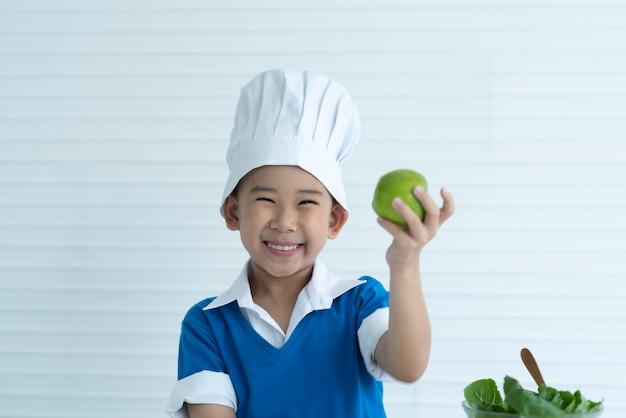 Drôle enfant mange une pomme, petit garçon beau avec une pomme verte, aliments santé, fruits, savourer un repas