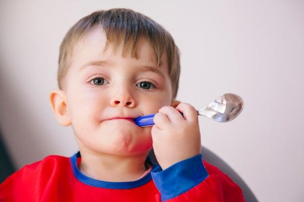 Drôle enfant tenant une cuillère avec sa bouche. mode de vie familial et sain.