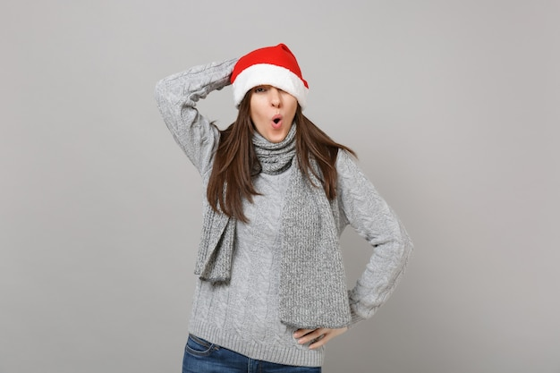 Drôle étonné jeune fille de santa en pull, écharpe couvrant les yeux avec un chapeau de noël, gardant la bouche grande ouverte isolée sur fond gris en studio. bonne année 2019 concept de fête de vacances célébration.