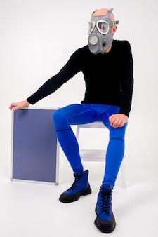 Drôle étrange homme en respirateur assis sur un escabeau avec un marqueur sur fond blanc