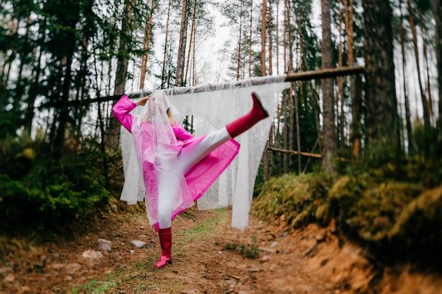 Drôle étrange jeune femme dans un imperméable rose posant avec une étamine dans la forêt