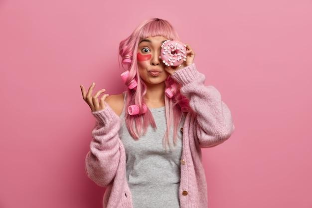 Drôle de femme asiatique aux cheveux roses a des rouleaux sur la tête, couvre les yeux avec un délicieux beignet sucré, porte des patchs de collagène pour réduire les rides