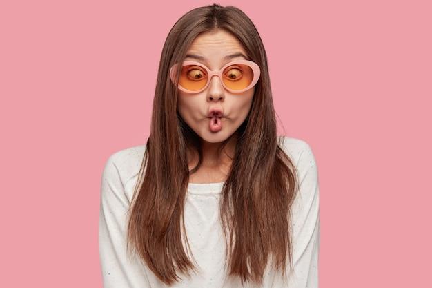 Drôle de femme caucasienne ludique fait des lèvres de poisson, a un regard fou, tente d'amuser un ami déprimé