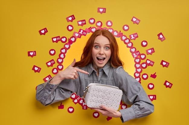 Drôle femme excitée pointant sur un sac à main, isolé sur un mur jaune, obtenir beaucoup de goûts