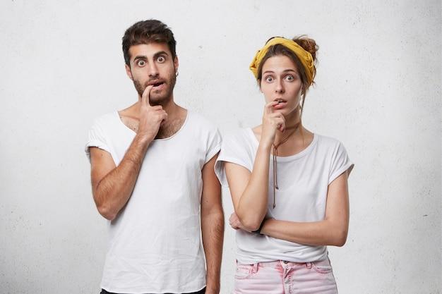 Drôle femme et homme en t-shirts blancs tenant leurs doigts dans la bouche à la surprise