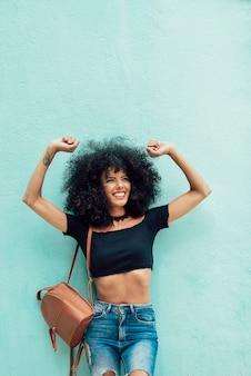Drôle femme noire aux cheveux afro, levant les bras à l'extérieur