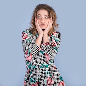 Drôle femme en robe touchant les joues