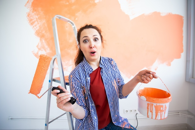 Drôle femme souriante peinture mur intérieur de la maison avec rouleau à peinture. redécoration, rénovation